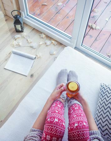 Schließen Sie herauf Ansicht von oben von den Händen der Frau, die Tasse Tee mit Zitrone halten. Hölzerne Patioplattform mit Fall verlässt als Hintergrund Standard-Bild - 74409379