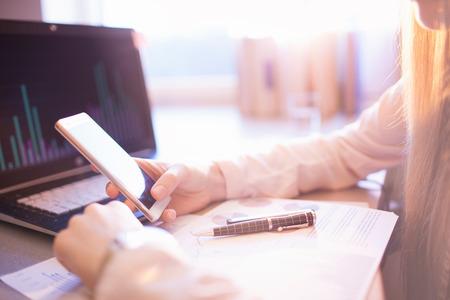 Geschäftsleute Kommunikationskonzept. Geschäftsfrau, die Smartphone, Laptop-Computer im Hintergrund verwendet Standard-Bild - 74409381