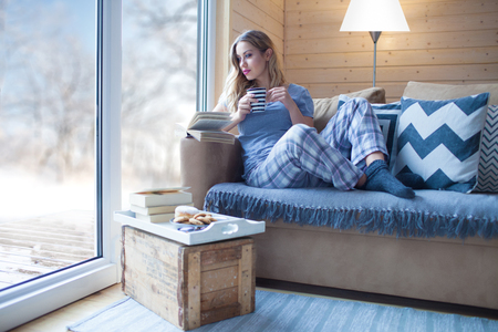 Young beautiful blonde woman with cup of coffee sitting home in living room by the window. Winter snow landscape view. Lazy day off concept Stok Fotoğraf - 75059961