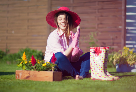 Woman gardener wearing straw hat have break while working with flowers in the garden Stock Photo