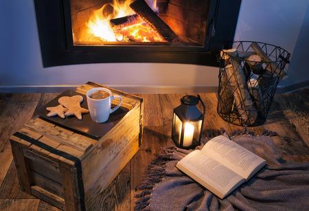 Kamin, Laterne, Kaffee, Süßigkeiten und ein Buch. Winter entspannende Heim Urlaub Konzept Standard-Bild - 75779856