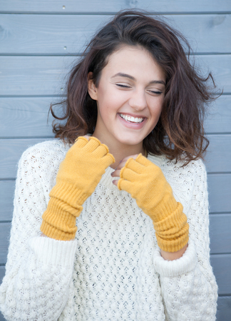 Beautiful natural young happy brunette woman wearing knitted sweater and gloves. Fall and winter fashion concept. photo