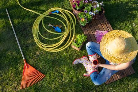 Frau mit einer Kaffeepause beim Arbeiten im Garten Standard-Bild - 74409384