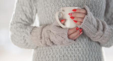 Frau, die die gestrickte Strickjacke und Handschuhe hält eine Schale heißen Kaffee, Energieeinsparung der humorvollen Hauptheizung trägt Standard-Bild - 74620214