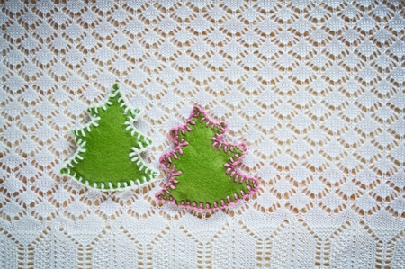 Christmas decoration with felt Christmas trees on openwork knitted background photo