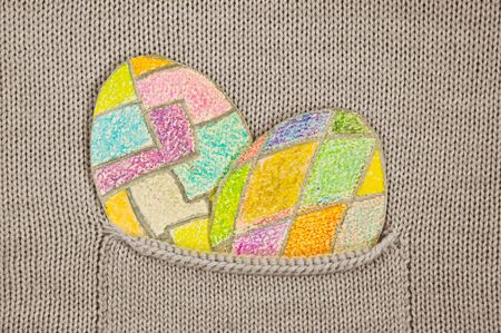 hide and seek: painted colorful Easter eggs in a knitted jacket pocket. Stock Photo