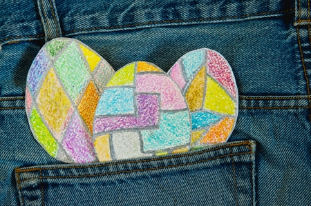 hide and seek: painted colorful Easter eggs in a jeans pocket.