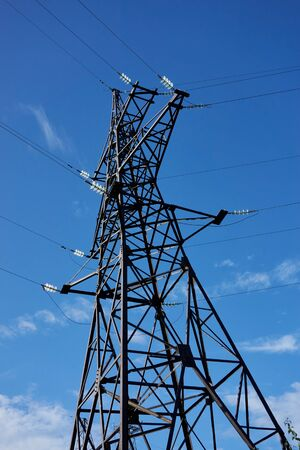 High-voltage power transmission towers under a blue sky Stock Photo