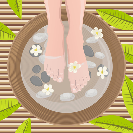 Female feet at spa pedicure procedure. Legs, flowers and ceramic bowl.