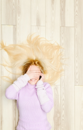 floor covering: Young woman covered eyes during phone conversation Stock Photo