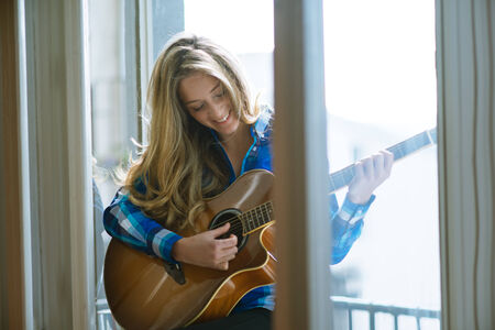 playing the guitar: Young woman playing guitar on window