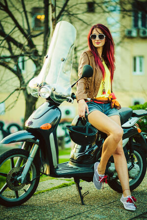 Young beautiful woman sitting on motorcycle photo
