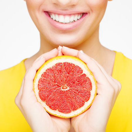 Young brunette with red grapefruit in her hand