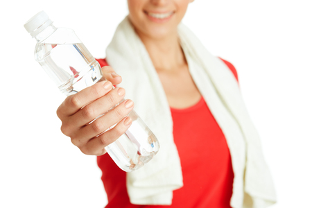 Young fitness woman giving bottle of water Stock Photo