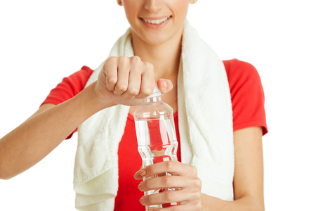 Young fitness woman opening bottle of water