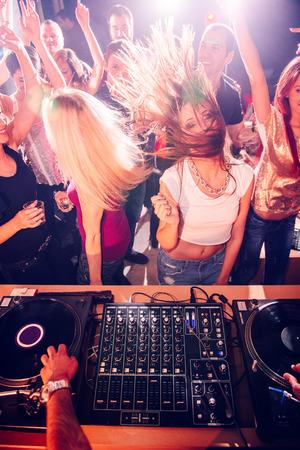 Party people na frente de DJ Imagens