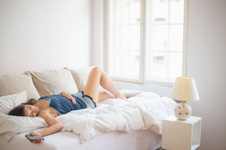 Lying in bed and holding mobile phone Stock Photo