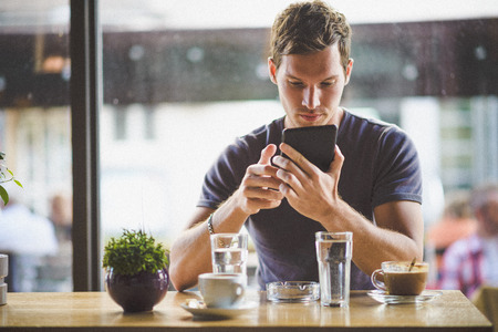 Jeune homme regardant tablette dans le café Banque d'images - 32277665
