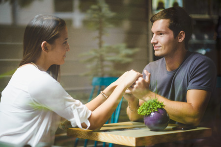 Young couple holding hands in cafe Stock Photo