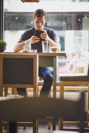 hombre tomando cafe: Hombre joven que ve la tableta en el caf�