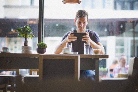cafe internet: Hombre joven que ve la tableta en el caf�