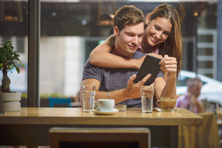 Young couple looking tablet Imagens