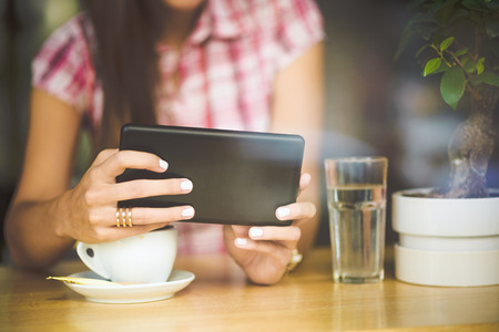 internet shop: Young woman in cafe looking in tablet