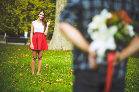 Man ready to give flowers to girlfriend Standard-Bild
