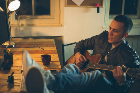 work from home: Man playing guitar at home after work