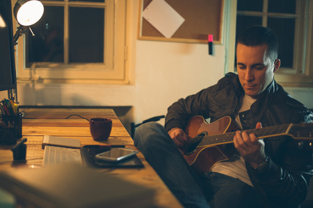chilling: Man playing guitar at home after work