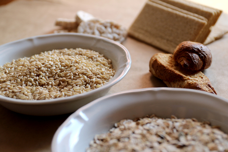 galletas integrales: Oats and rice in a bowl close-up. Rice cakes and bread in background.