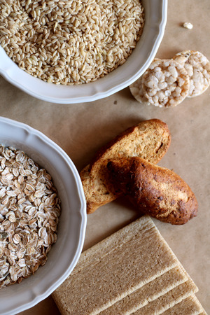 galletas integrales: Oats and rice in a bowl. Rice cakes and bread in background. Food high in carbohydrates.