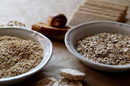 Oats and rice in a bowl. Rice cakes and bread in background. Food high in carbohydrates.