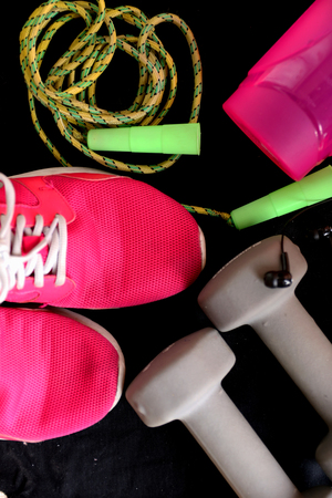 Sport equipment on black background. Sport wear, sport fashion, sport accessories. Sneakers, athletic shoes, dumbbells, headphones, earphones, bottle of water, jumping rope. Top view. Stock Photo