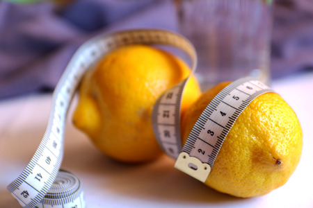 Healthy eating, drinks, diet, detox concept - close up of two lemons and water in glass with meter. Lemon water, losing weight. Loss weight fruit diet isolated. Fruit with meter, diet concept..