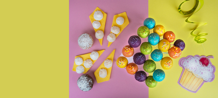 Top view of cake pops on a bright yellow-pink background, decorated for birthday celebration, with bright yellow copy space. Selective focus Stock Photo