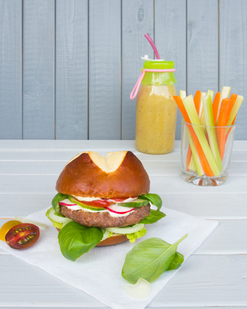 Burger with cutlet with vegetables, and green smoothie with sticks of celery and carrots on and white wooden background