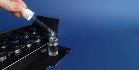 Fingers hold pipette with sparkling drop of cosmetic liquid in flacon,copy space