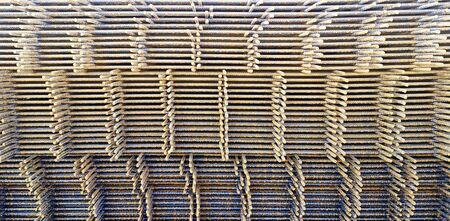 Bulk construction rebar for concrete pouring. Welded wire mesh made of iron bars.Closeup of steel industrial rebar texture.Straight rows of armature,rust-coated fittings,ready to be moved with tower crane.Background or wallpaper