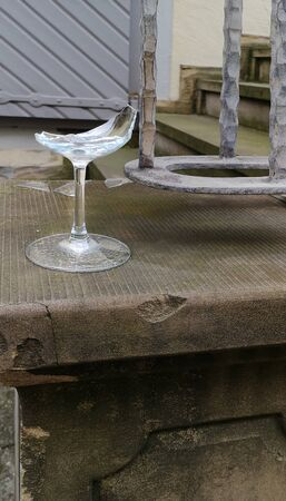 Broken wine glass standing on ancient partly broken stone pedestal,against background of stairs and iron curved railing 版權商用圖片