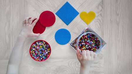 Step-by-step instructions for thermo mosaics: step 2.Pair of kid's hands,several circle and square forms with pins,container and lid with colorful beads on wooden background.Home game for children.