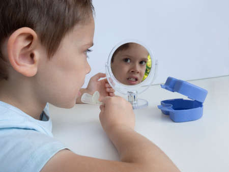 5-year-old boy on white backdrop with round mirror,which reflects his face,inserts orthodontic silicone device to correct the bite for small children into his mouth.Blue dental plates holder on table.