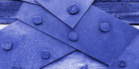 Closeup texture of rusty iron sheets bolted to aged planks in blue purple tones.Concept of banning,prohibition, closing Stockfoto