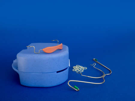 Orthodontic devices: removable metal braces and rubberized flesh-colored plastic cap,-for upper and lower teeth,dental rubber bands and box on dark blue background.Selective focus.Copy space,banner. Zdjęcie Seryjne