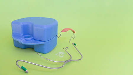 Orthodontic devices: removable metal braces,rubberized flesh-colored plastic cap,-for upper and lower teeth,dental rubber bands and box on yellow green background.Selective focus.Copy space,banner.
