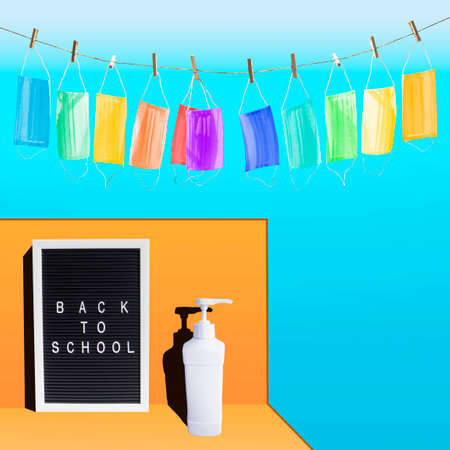 Back to school word on letter board,garland of colorful medical masks,sanitizer dispenser bottle on blue,orange backdrop Archivio Fotografico