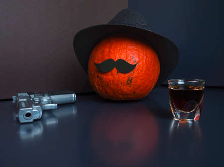Halloween pumpkin as a man with mustache, wearing black hat on dark background, gray pistol, shot glass of spirits. Фото со стока