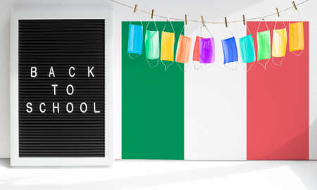 Back to school words on letter board, garland of colorful medical masks, like holiday flags on backdrop of the flag of Italy.Concept of new education period start in Italy new hygiene normal.Copy space.