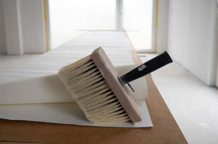 Wide paint brush for glue with wooden base for bristle, black handle, several sheets of white wallpaper unfolded in length on table for pasting against white wall, floor-to-ceiling French window in room.