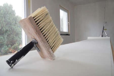 Wide paint brush for glue with wooden base for bristle, black handle, sheet of white wallpaper unfolded in length on table for pasting against renovating room with window, ladder in backgdrop.Copy space. Standard-Bild - 156564497